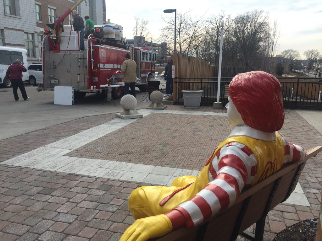 Foreground: Ronald McDonald statue sitting on a bench. Background: Volunteers from St. Joseph KofC serving food from a modified fire truck.
