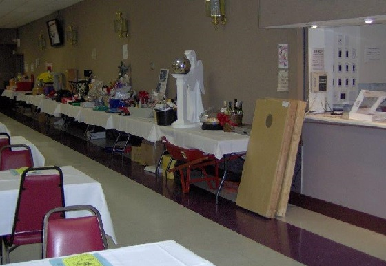 Oral Auction Items Displayed. Prominently showing angel statue with globe, game sets, gift baskets, priceless home-made deserts, tools, etc.